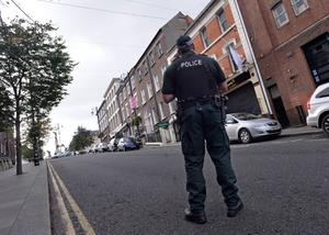 A heavily armed police officer in Shipquay Street, Derry, where Barry McCrory was shot dead in a city centre apartment . Photo Stephen Davison/Pacemaker