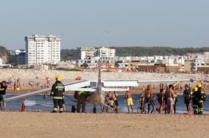 Firefighters stand next to a small plane after an emergency landing on Sao Joao beach in Costa da Caparica, outside Lisbon
