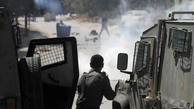 An Israeli soldier aims his weapon at a Palestinian during clashes in Hawara village near the West Bank city of Nablus on Friday, July 25, 2014. (AP Photo/Nasser Ishtayeh)