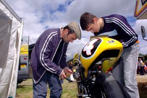 PACEMAKER, BELFAST, 20/6/2004:  The legend lives on- 5-time TT winner Robert Dunlop gets some help from his son, William as he prepares his 125cc Honda for the Athea road races in Co Limerick. PICTURE BY STEPHEN DAVISON