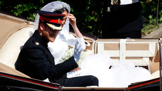 Britain's Prince Harry, Duke of Sussex (L) and his wife Meghan, Duchess of Sussex (R) begin their carriage procession in the Ascot Landau Carriage after their wedding ceremony at St George's Chapel, Windsor Castle, in Windsor, on May 19, 2018.  / AFP PHOTO / POOL AND AFP PHOTO / Odd ANDERSENODD ANDERSEN/AFP/Getty Images