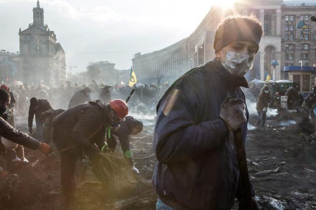 KIEV, UKRAINE - FEBRUARY 20: Anti-governent protesters clear ashes and debris from a newly occupied portion of Independence Square on February 20, 2014 in Kiev, Ukraine. Dozens of protesters were reportedly been killed after violence flared again between police and anti-government protesters, who are calling to oust President Viktor Yanukovych over corruption and an abandoned trade agreement with the European Union.  (Photo by Brendan Hoffman/Getty Images)