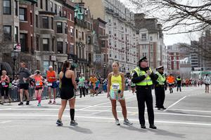 BOSTON, MA - APRIL 15:  Police and runners stand near Kenmore Square after two bombs exploded during the 117th Boston Marathon on April 15, 2013 in Boston, Massachusetts. Two people are confirmed dead and at least 28 injured after at least two explosions went off near the finish line to the marathon.  (Photo by Alex Trautwig/Getty Images)