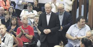 Deputy First Minister Martin McGuinness and Colin Parry are applauded as they attend a discussion as part of Feile an Phobail