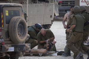 Israeli soldiers give medical care to soldiers who where wounded during an offensive in Gaza on July 20, 2014 at the Israeli-Gaza border. (Photo by Lior Mizrahi/Getty Images)