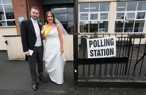 Alliance candidate for West Belfast Sorcha Eastwood casts her vote in the 2017 General Election, with her husband, Dale Shirlow, at a polling station in Lisburn, Northern Ireland, still wearing her wedding dress after they were married earlier in the day.Brian Lawless/PA Wire