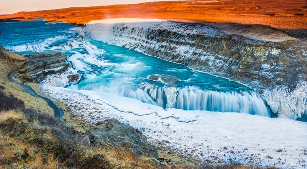 Beautiful Nordic landscape from spectacular Iceland including mighty Gullfoss waterfall partly frozen in ice.