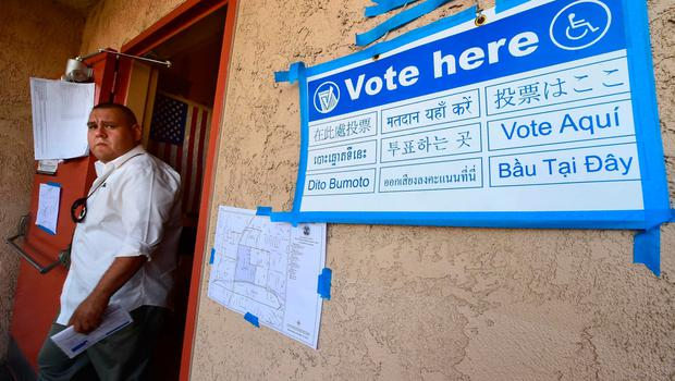 "A multi-language""Vote Here sign"" leads to the voting room as a man who'd just cast his vote steps out on election day at Brooklyn Avenue Elementary School in the primarily Latino East LA neighborhood of Boyle Heights on November 8, 2016 in Los Angeles, California. / AFP PHOTO / Frederic J. BROWNFREDERIC J. BROWN/AFP/Getty Images"