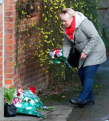 A woman lays flowers outside the Goring house of George Michael in Oxfordshire as the pop superstar has died at the age of 53 from suspected heart failure.