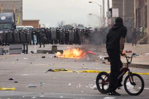 BALTIMORE, MD - APRIL 27:  With Baltimore Police officers in riot gear lining the street, a man stands at the corner of Pennsylvania Avenue and North Avenue , April 27, 2015 in Baltimore, Maryland. Riots have erupted in Baltimore following the funeral service for Freddie Gray, who died last week while in Baltimore Police custody. (Photo by Drew Angerer/Getty Images)