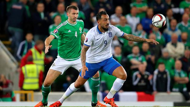 Greece's Konstantinos Mitroglou and Northern Ireland's Gareth McAuley (left) battle for the ball during the UEFA European Championship Qualifying match at Windsor Park, Belfast. PRESS ASSOCIATION Photo. Picture date: Thursday October 8, 2015. See PA story SOCCER N Ireland. Photo credit should read: Niall Carson/PA Wire.