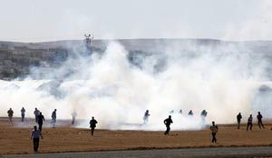 Protesters run away from tear gas during a pro-Kurdish demonstration in solidarity with the people of Kobani, near the Mursitpinar border crossing on the Turkish-Syrian border on October 7, 2014 near the southeastern town of Suruc in Sanliurfa province, Turkey.   (Photo by Stringer/Getty Images)