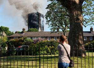 A man photographs a fire that has engulfed the 27-storey Grenfell Tower in west London.   Rick Findler/PA Wire