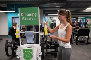 A gym member uses the cleaning station at PureGym in Leamington Spa (Jacob King/PA)
