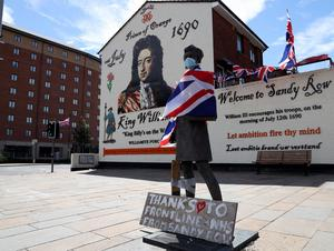 A statue at Sandy Row decorated with a Union Jack and a face mask.  Photo Pacemaker Press