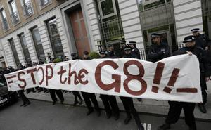 Demonstrators hold up a banner against the G8 outside the headquarters of British based oil multinational BP during a protest  in London, Tuesday, June  11, 2013 .The protestors were demonstrating against the upcoming  G8 summit in Northern Ireland on June 17 and 18.(AP Photo/Alastair Grant)