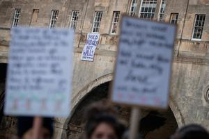"BATH, ENGLAND - JANUARY 20:  A groip of protestors gather beneath a banner reading ""Build bridges not walls""  dropped from a window on Pulteney Bridge on January 20, 2017 in Bath, England. The banner drop in Bath is part of a series of events across the world aimed at expressing disproval at today's inauguration of Donald Trump as the 45th U.S. president.  (Photo by Matt Cardy/Getty Images)"
