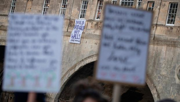 """BATH, ENGLAND - JANUARY 20:  A groip of protestors gather beneath a banner reading """"Build bridges not walls""""  dropped from a window on Pulteney Bridge on January 20, 2017 in Bath, England. The banner drop in Bath is part of a series of events across the world aimed at expressing disproval at today's inauguration of Donald Trump as the 45th U.S. president.  (Photo by Matt Cardy/Getty Images)"""