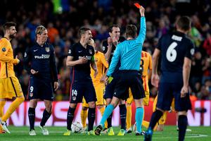 German referee Felix Brych (C) shows a red card to Atletico Madrid's forward Fernando Torres (2L) as Atletico Madrid's Uruguayan defender Diego Godin and Atletico Madrid's midfielder Gabi(3L) argue during the UEFA Champions League quarter finals first leg football match FC Barcelona vs Atletico de Madrid at the Camp Nou stadium in Barcelona on April 5, 2016. / AFP PHOTO / JOSEP LAGOJOSEP LAGO/AFP/Getty Images