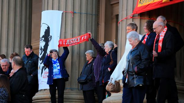 LIVERPOOL, ENGLAND - APRIL 27:  People hold up a banner stating Jusutice as they gather outside Liverpool's Saint George's Hall to attend a vigil for the 96 victims of the Hillsborough tragedy on April 27, 2016 in Liverpool, England. The civic commemoration event marks the outcome of the fresh inquests into the 1989 Hillsborough disaster, in which 96 football supporters were crushed to death, and concluded yesterday with a verdict of unlawful killing. Relatives, Liverpool supporters and members of the public are taking part in the vigil at St George's Hall where a candle is lit for each of the 96 victims who lost their lives during a crush at the Hillsborough football ground in Sheffield, South Yorkshire in 1989..  (Photo by Christopher Furlong/Getty Images)