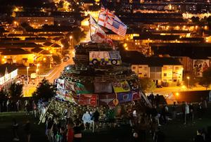 Flags on a bonfire, in the bogside area of Londonderry, which is traditionally torched on August 15 to mark a Catholic feast day celebrating the assumption of the Virgin Mary into heaven, but in modern times the fire has become a source of contention and associated with anti-social behaviour. PRESS ASSOCIATION Photo. Picture date: Tuesday August 15, 2017. Disorder flared in Londonderry on Monday night as bonfire-builders attacked police and members of the public. Police said those gathered at the controversial fire site in Derry's Bogside threw rocks and stones at local people before targeting police with petrol bombs and other missiles. See PA story ULSTER Bonfire. Photo credit should read: Niall Carson/PA Wire