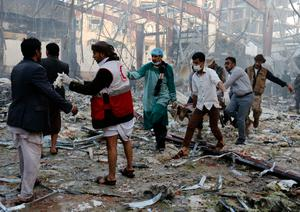 Medics carry the body of a victim of a Saudi-led coalition airstrike in Sanaa, Yemen, Saturday, Oct. 8, 2016. Yemeni security and medical officials say at least 45 people have been killed in a Saudi-led coalition airstrike that targeted a funeral hall in the capital, Sanaa. The officials say at least another 100 have been wounded in the Saturday strike. (AP Photo/Osamah Abdulrhman)