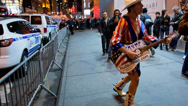 "A ""Naked Cowboy"" performer sings about Republican presidential nominee Donald Trump outside Trump Tower in New York City on election day November 8, 2016. Hillary Clinton and Donald Trump were running neck and neck in early results November 8th as polling stations closed in the eastern United States, with the world waiting anxiously to see who will win the historic White House clash.  / AFP PHOTO / DOMINICK REUTERDOMINICK REUTER/AFP/Getty Images"