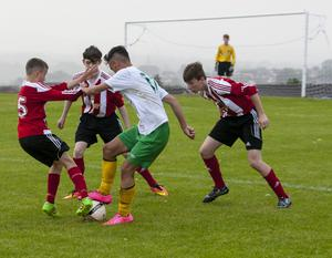 Donegal's Finian O'Donnell shows some neat footwork as three Carniney Youths defenders close in during Thursday's Hughes Insurance Foyle Cup clash. FC04-M2-04