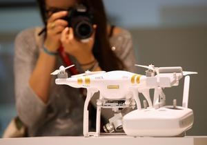 BERLIN, GERMANY - SEPTEMBER 03:  Visitors look at a Phantom 3 Professional quadcopter drone at the DJI stand during a press day at the 2015 IFA consumer electronics and appliances trade fair on September 3, 2015 in Berlin, Germany. The 2015 IFA will be open to the public from September 4-9.  (Photo by Sean Gallup/Getty Images)