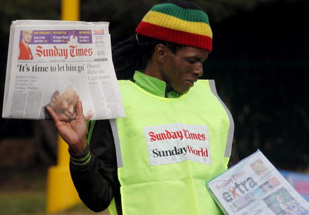 A newspaper seller holds the Sunday Times newspaper with the headline 'It's time to let him go' referring to words spoken by long-time friend of former president Nelson Mandela, Andrew Mlangeni, in Johannesburg, South Africa, Sunday June 9, 2013.  Mlangeni uttered the words when he learnt that the former president had been hospitalized for a fourth time since December. (AP Photo/Denis Farrell)