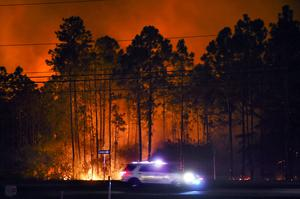 A sheriff's vehicle travels along US Highway 98 in Walton County as wildfires burn nearby (Devon Ravine/Northwest Florida Daily News via AP)