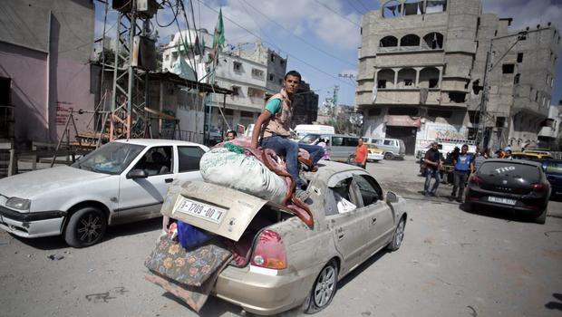 Palestinians salvage what little of their belongings they could from their homes during a 12-hour cease-fire in Gaza City's Shijaiyah neighborhood, Saturday, July 26, 2014.  (AP Photo/Khalil Hamra)