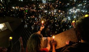 People hold candles during a vigil at Thanksgiving Square in downtown Dallas, Monday, Jan. 30, 2017. People gathered to protest against President Donald Trump's executive order temporarily banning immigrants from seven Muslim-majority countries from entering the U.S. and suspending the nationÄôs refugee program. (AP Photo/LM Otero)