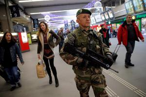 A French soldier patrols at the Montparnasse railway station in Paris, France, Wednesday, Jan. 7, 2015. France reinforced security at houses of worship, stores, media offices and transportation after masked gunmen stormed the offices of a French satirical newspaper Wednesday, killing at least 11 people before escaping, police and a witness said. The weekly has previously drawn condemnation from Muslims. (AP Photo/Christophe Ena)