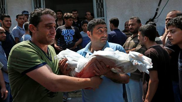 Palestinians carry a child from the al-Halaq family, killed Sunday by an Israeli strike at their house in Gaza City, during their funeral, Monday, July 21, 2014. (AP Photo/Lefteris Pitarakis)