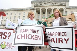 PACEMAKER BELFAST  04/09/2015 Farmers, processers and retailers have held a protest at Stormont to highlight volatility in prices. It was organised by the Ulster Farmers' Union (UFU) and comes ahead of Monday's key EU farm ministers summit on the crisis in the dairy industry. Joy Rolson and jane Rolson, Dairy and poultry farmers  protest outside Stormont. Picture Matt Bohill.