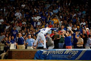 CHICAGO, IL - AUGUST 16: Anthony Rizzo #44 of the Chicago Cubs makes a catch for an out against the Milwaukee Brewers while standing on the wall during the fifth inning in game two of a double header at Wrigley Field on August 16, 2016 in Chicago, Illinois.  (Photo by Jon Durr/Getty Images) *** BESTPIX ***