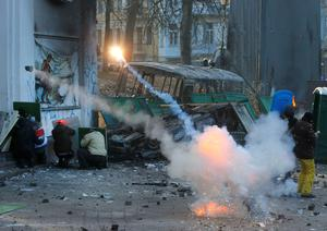 Protesters clash with police, in central Kiev, Ukraine, Monday, Jan. 20, 2014. Protesters erected barricades in central Kiev with the sound of stun grenades heard in the freezing air as police try to quell anti-government street protests. (AP Photo/Sergei Grits)