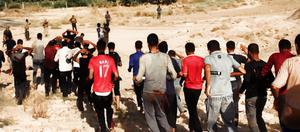 This image posted on a militant website on Saturday, June 14, 2014, which has been verified and is consistent with other AP reporting, appears to show militants from the al-Qaida-inspired Islamic State of Iraq and the Levant (ISIL) leading captured Iraqi soldiers wearing plain clothes to an open field moments before shooting them in Tikrit, Iraq. The Islamic militant group that seized much of northern Iraq has posted photos that appear to show its fighters shooting dead dozens of captured Iraqi soldiers in a province north of the capital Baghdad. Iraq's top military spokesman Lt. Gen. Qassim al-Moussawi confirmed the photos authenticity on Sunday and said he was aware of cases of mass murder of Iraqi soldiers. (AP Photo via militant website)