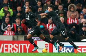 """Liverpool's Jordon Ibe (left) celebrates with Roberto Firmino after scoring his side's first goal during the Capital One Cup, semi final, first leg match at The Britannia Stadium, Stoke. PRESS ASSOCIATION Photo. Picture date: Tuesday January 5, 2015. See PA story SOCCER Stoke. Photo credit should read: Martin Rickett/PA Wire. RESTRICTIONS: EDITORIAL USE ONLY No use with unauthorised audio, video, data, fixture lists, club/league logos or """"live"""" services. Online in-match use limited to 75 images, no video emulation. No use in betting, games or single club/league/player publications."""