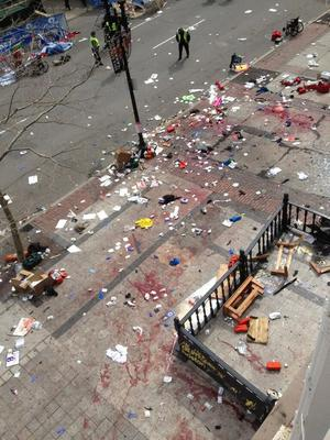 This photo provided by Bruce Mendelsohn shows the scene after two explosions occurred during the 2013 Boston Marathon in Boston, Monday, April 15, 2013. Two explosions shattered the euphoria of the Boston Marathon finish line on Monday, sending authorities out on the course to carry off the injured while the stragglers were rerouted away from the smoking site of the blasts. (AP Photo/ Bruce Mendelsohn) MANDATORY CREDIT