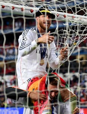 LISBON, PORTUGAL - MAY 24:  Sergio Ramos of Real Madrid cuts the goal netting as he celebrates during the UEFA Champions League Final between Real Madrid and Atletico de Madrid at Estadio da Luz on May 24, 2014 in Lisbon, Portugal.  (Photo by Shaun Botterill/Getty Images)