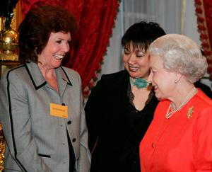 Queen Elizabeth II meeting TV presenter Cilla Black (left) in 2005. Kirsty Wigglesworth/PA Wire.