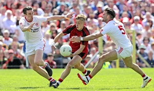 Too hot : Down's Jerome Johnston feels the pressure from Conal McCann and Tiernan McCann of Tyrone