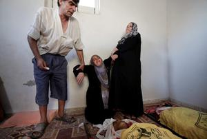 Palestinians help a woman overcome by emotion during the funeral of Shaher al-Najar, left, and his brother Bassem al-Najar, right, killed in an Israeli strike, at the family house in Jebaliya refugee camp, northern Gaza Strip, Wednesday, July 30, 2014. (AP Photo/Lefteris Pitarakis)