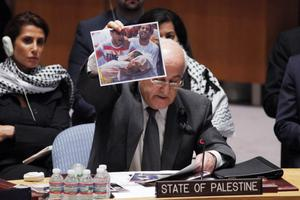 NEW YORK, NY - JULY 22:  Riyad H. Mansour, Palestine's Ambassador to the United Nations, holds up a picture from the Israeli operation in Gaza during a Security Council meeting at the UN on July 22, 2014 in New York City. The Israeli operation in the Gaza Strip is entering the third week with 27 Israeli's dead and over 500 people killed in Gaza, the vast majority being civilians.  (Photo by Kena Betancur/Getty Images)