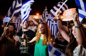 People celebrate in Athens on July 5, 2015 after the first exit-polls of the Greek referendum. Over 60 percent of Greeks rejected further austerity dictated by the country's EU-IMF creditors in a referendum, results from 20 percent of polling stations showed