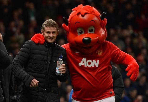 MANCHESTER, ENGLAND - JANUARY 28:  Cardiff City Manager Ole Gunnar Solskjaer is greeted by mascot Fred the Red prior to the Barclays Premier League match between Manchester United and Cardiff City at Old Trafford on January 28, 2014 in Manchester, England.  (Photo by Michael Regan/Getty Images)