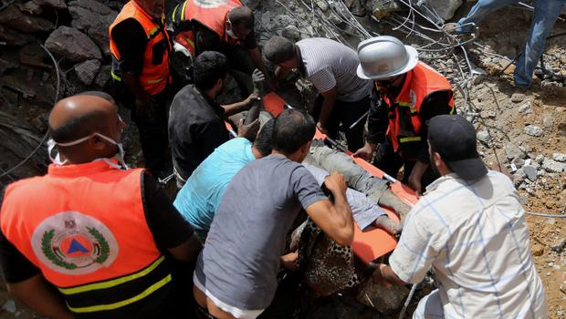 Palestinian medics carry a body of a man after they found him under the rubble of a home destroyed by an Israeli strike in Khan Younis in the southern Gaza Strip, Friday, July 25, 2014.  (AP Photo/Hatem Moussa)
