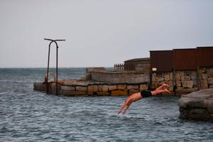 A man takes a swim at Sandycove, southeast of Dublin on the Irish Sea coast, on October 16, 2017 as Ireland braces for the passing of the storm Ophelia.  / AFP PHOTO / Ben STANSALLBEN STANSALL/AFP/Getty Images